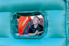 Cute little boy playing in a jumping castle. Peering through the net covering the window in the side grinning at the camera Royalty Free Stock Photos