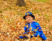Cute little boy playing with leaves in fall Royalty Free Stock Photos