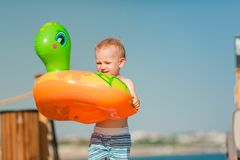 Cute little boy playing with life buoy at the seaside Stock Photo