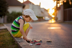 Cute little boy, playing with little toy cars on the street on s Royalty Free Stock Images