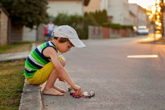 Cute little boy, playing with little toy cars on the street on s Stock Photo