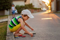 Cute little boy, playing with little toy cars on the street on s Stock Images