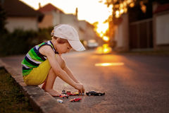 Cute little boy, playing with little toy cars on the street on s Stock Photography