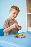 Cute little boy playing with modelling clay in classroom Stock Photography