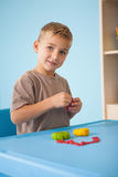 Cute little boy playing with modelling clay in classroom Royalty Free Stock Image