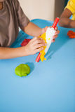 Cute little boy playing with modelling clay in classroom Stock Photo