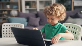 Cute little boy playing with modern laptop pushing buttons and smiling at home. Cute little boy is playing with modern laptop pushing buttons and smiling stock footage
