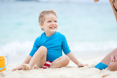 Cute little boy playing with mother on the beach Stock Photo