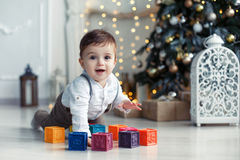 Cute little boy playing near the Christmas tree with colored cubes Royalty Free Stock Photo