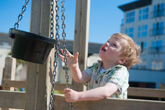 Cute little boy playing outdoors with bucket and chain Royalty Free Stock Image