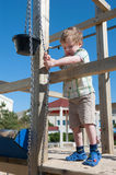 Cute little boy playing outdoors with bucket and chain Royalty Free Stock Photography