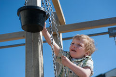 Cute little boy playing outdoors with bucket and chain Royalty Free Stock Photo