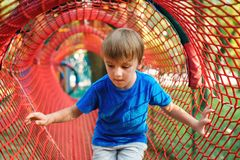 Cute little boy playing outdoors. Child having fun in tunnel at the modern playground. Happy childhood. Summer holidays stock image