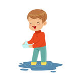 Cute little boy playing with paper boat in a water puddle cartoon vector Illustration Royalty Free Stock Photos
