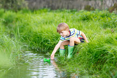 Cute little boy playing with paper boats by a river Stock Photography