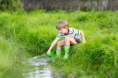 Cute little boy playing with paper boats by a river Royalty Free Stock Photography