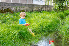 Cute little boy playing with paper boats by a river Royalty Free Stock Image