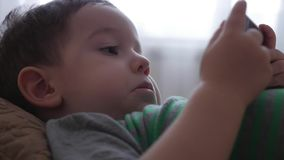 Cute little boy playing on the phone, lying on his sofa, playing with the tablet computer. Cute little boy playing on the phone, lying on his sofa, playing with stock footage