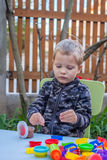 Cute little boy playing with plasticine. In the garden Stock Photos