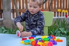 Cute little boy playing with plasticine. In the garden Royalty Free Stock Photo