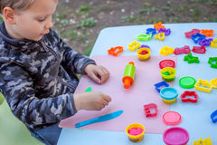 Cute little boy playing with plasticine. In the garden Royalty Free Stock Photos