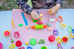 Cute little boy playing with plasticine. In the garden Stock Photography