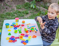 Cute little boy playing with plasticine. In the garden Stock Images