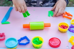 Cute little boy playing with plasticine. In the garden Stock Image