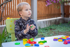 Cute little boy playing with plasticine. In the garden Royalty Free Stock Image