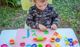 Cute little boy playing with plasticine. In the garden Stock Photo