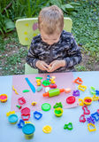 Cute little boy playing with plasticine. In the garden Royalty Free Stock Images