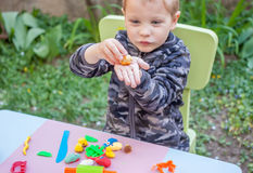 Cute little boy playing with plasticine. In the garden Royalty Free Stock Photography