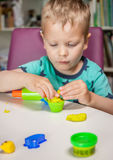 Cute little boy playing with plasticine. At home Royalty Free Stock Photo