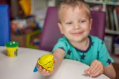 Cute little boy playing with plasticine. At home Stock Images