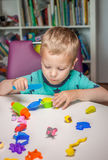 Cute little boy playing with plasticine. At home Royalty Free Stock Photos