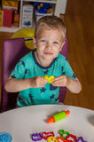 Cute little boy playing with plasticine. At home Royalty Free Stock Images