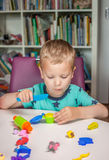 Cute little boy playing with plasticine. At home Stock Photography