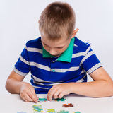 Cute little boy playing puzzles at the table Royalty Free Stock Photography