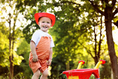 Cute little boy playing with a red wheelbarrow in summer park Stock Image