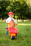 Cute little boy playing with a red wheelbarrow in summer park Royalty Free Stock Photo