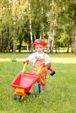 Cute little boy playing with a red wheelbarrow in summer park Stock Photography