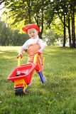 Cute little boy playing with a red wheelbarrow in summer park Stock Images