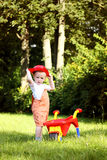 Cute little boy playing with a red wheelbarrow in summer park Royalty Free Stock Images