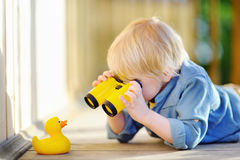 Cute little boy playing with rubber duck and plastic binoculars outdoors. Blonde hair child having fun with toy duckling Stock Images