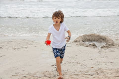 Cute little boy playing in sand on beach in summer Royalty Free Stock Photo