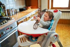 Cute little boy, playing sitting in chair in a sunny living kitchen, baby boy smiling happily royalty free stock photography