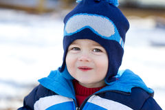 Cute little boy playing in the snow. The photograph is a portrait of a very cute, handsome little boy playing in the snow. He is wearing a blue coat and hat and royalty free stock photography