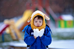 Cute little boy, playing with snow in the park, playground Royalty Free Stock Images