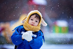 Cute little boy, playing with snow in the park, playground Stock Images