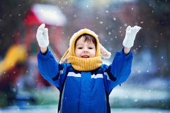 Cute little boy, playing with snow in the park, playground Stock Photos